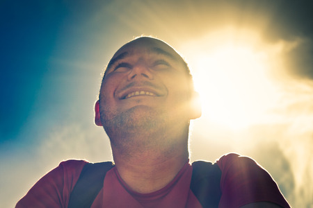 Portrait of young smiling man over sunny sky. photo