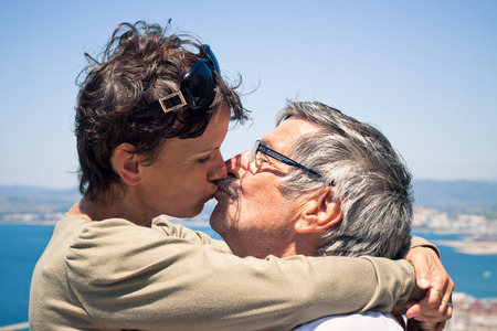 love kissing: Middle aged woman and senior man in love kissing outdoors.