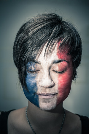 Portrait of woman with flag of France painted on face and closed eyes. photo