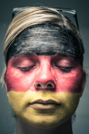 Portrait of woman with flag of Germany painted on face and closed eyes. photo