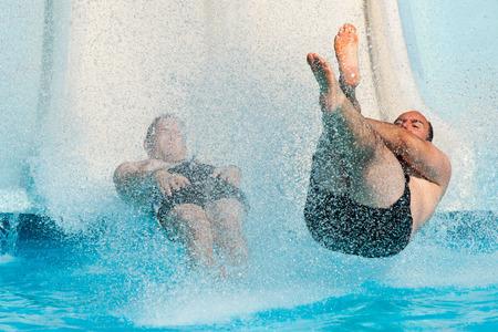 People having fun, sliding at water park.