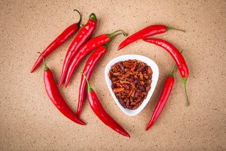 capsicums: Fresh and dried red hot chili peppers on wooden table.
