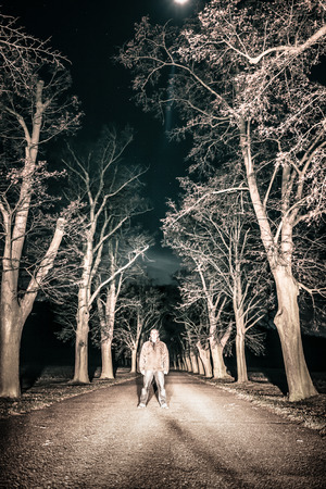 person standing: Scary horror person standing in night landscape