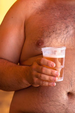 Detail of shirtless obese man holding beer. photo