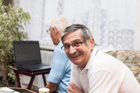 Two happy seniors learning to use a computer. photo