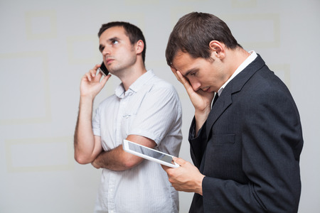 Two businessmen using digital tablet and smartphone. photo