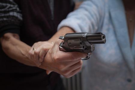 violencia intrafamiliar: Primer plano de la lucha pareja de ancianos con una pistola. Foto de archivo