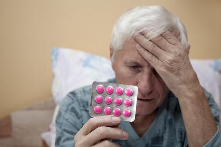 Senior man with headache holding painkillers.