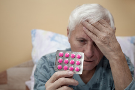 Senior man with headache holding painkillers.