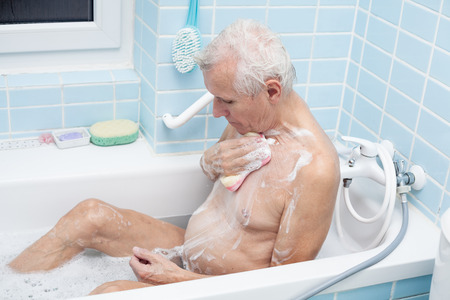 bathing man: Senior man washing his body with soap sponge in bath.