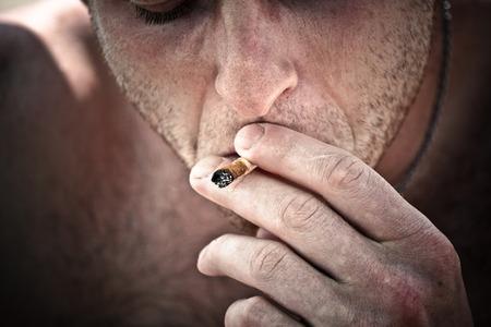 Close up of young man smoking hashish joint. photo