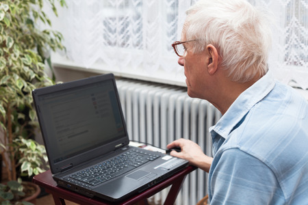 Senior man surfing on the internet at home. photo
