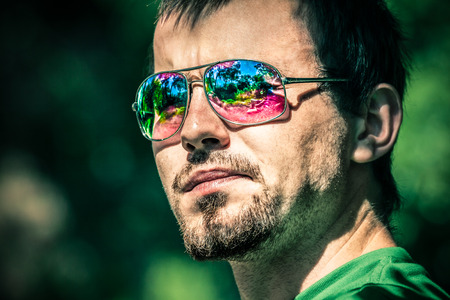 Portrait of young man wearing sunglasses with colourful reflection photo