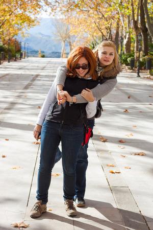 two women hugging: Two young happy women having fun in park Stock Photo