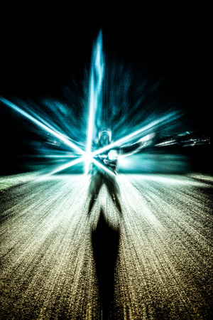 Abstract photo of a man and light effects over dark background photo