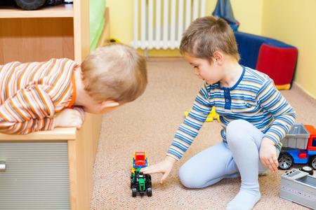 hermanos jugando: Dos niños juegan con los juguetes en el hogar Foto de archivo