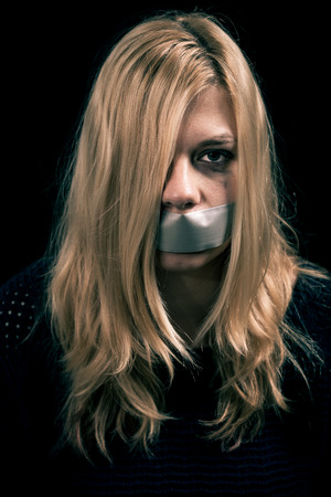abused women: Portrait of scared kidnapped woman hostage with tape over her mouth