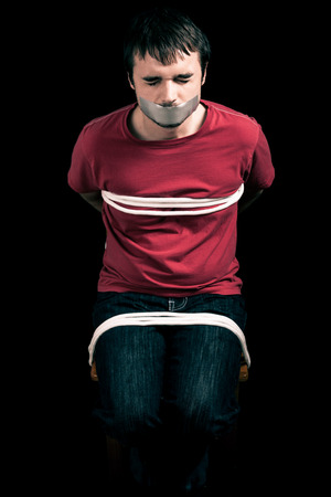 convict: Kidnapped man hostage with tape over mouth and tied up with rope Stock Photo