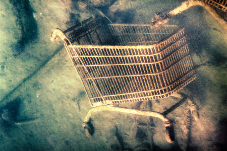 Abstract creative photo of shopping trolley discarded on the sea bottom  photo