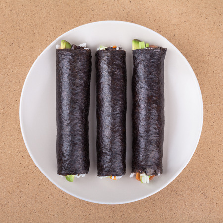 Three Sushi rolls wrapped in Nori seaweed on plate, over wooden background