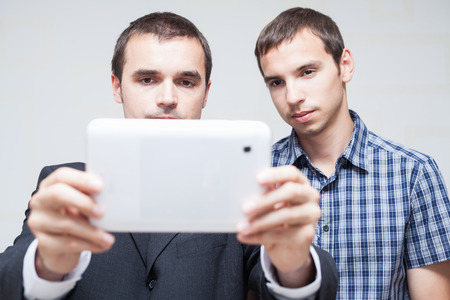Two serious businessmen looking at digital tablet  photo