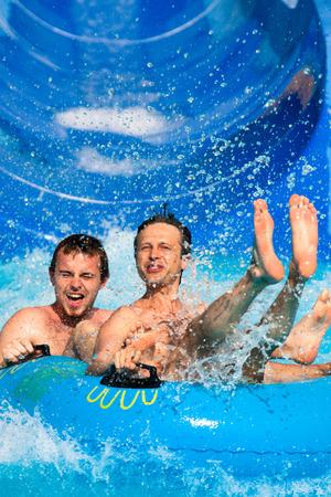 Two men having fun, people water slide at aqua park.