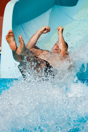 WATER SLIDE: Man having fun, sliding at water park.