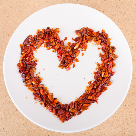 Hot love concept, red chili peppers on plate arranged in heart shape. photo