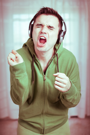Crazy casual young man with headphones singing.