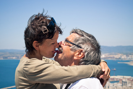 older couple: Happy middle aged woman and senior man in love kissing outdoors. Stock Photo