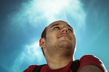 overweight man: Pensive man thinking over bright blue sky