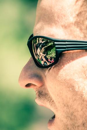 visage profil: Détail de l'homme face à la bouche ouverte des lunettes de soleil de sport