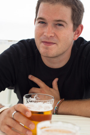 Close up of young man with glass of beer. photo