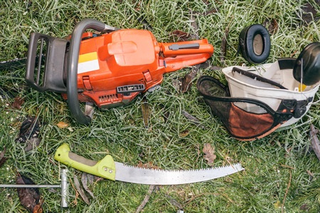 Chainsaw and pruning handsaw lying in the garden. photo
