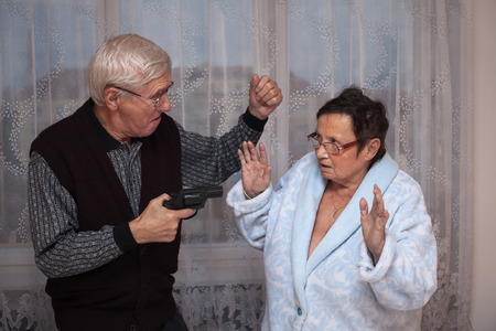 couple fight: Mad senior couple fighting with a gun.