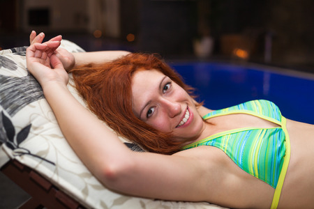 Happy woman wearing bikini and relaxing in wellness and spa swimming pool. photo