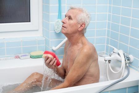 Senior man washing his body with soap sponge in bath. photo