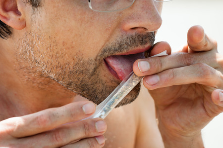 doped: Close up of man rolling hashish joint. Stock Photo