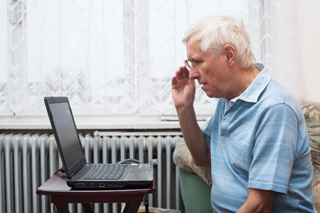 old man sitting: Senior man learning to use a computer at home.