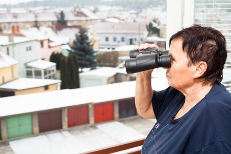 birdwatcher: Senior woman with binoculars looking out from window.
