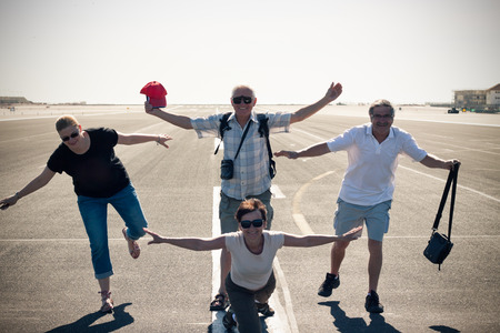 Funny group of tourist people imitating airplane at the airport runway. photo