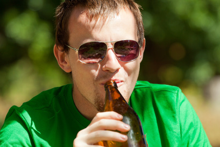 Young happy man drinking beer from bottle outdoors. photo