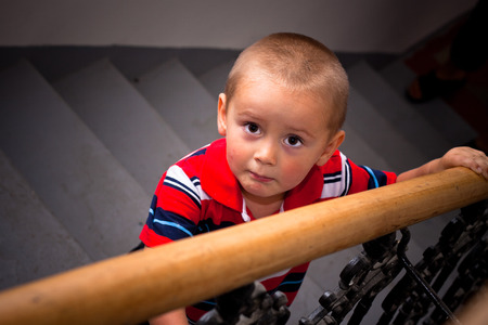 Scared looking boy on stairs. photo