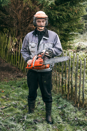 Portrait of professional gardener with chainsaw standing in the garden.