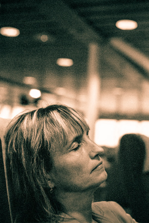 Closeup of middle aged woman sleeping in public transport. Toned grainy 35mm film scan. photo