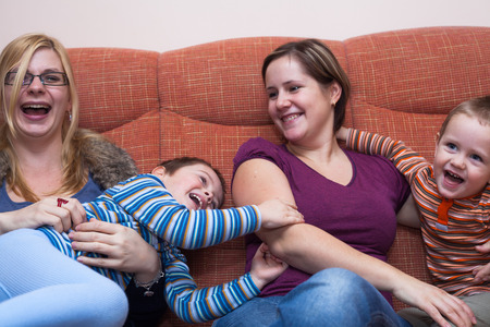 lesbian love: Two happy women playing with children at home Stock Photo