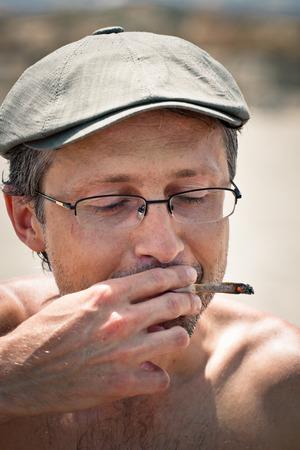 Close up of a man smoking hashish joint. photo