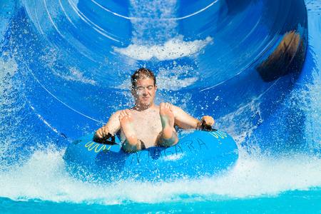 aqua park: Man having fun, sliding at water park.