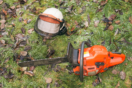 chainsaw: Chainsaw and helmet lying on the ground.