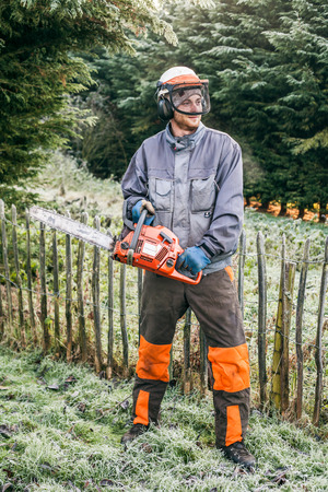 chainsaw: Portrait of professional gardener with chainsaw standing in the garden.